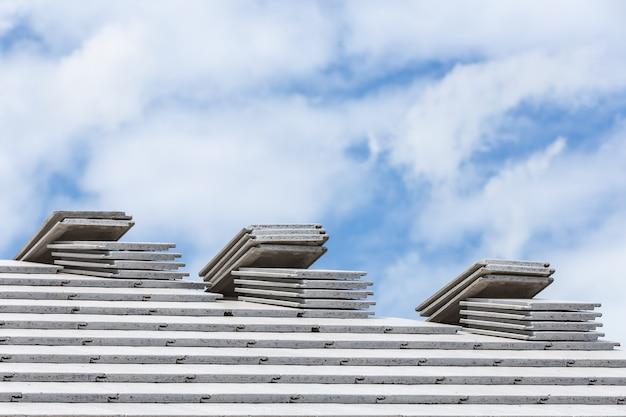 Toit en tuiles de couleur gris béton en construction avec des piles sur le toit