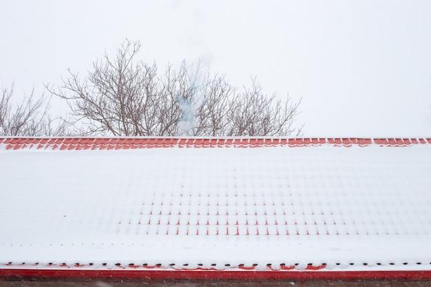 Le toit en tuiles métalliques est recouvert de chutes de neige. toiture fiable en hiver.