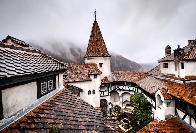 Toits du château de bran sur fond de montagnes brumeuses