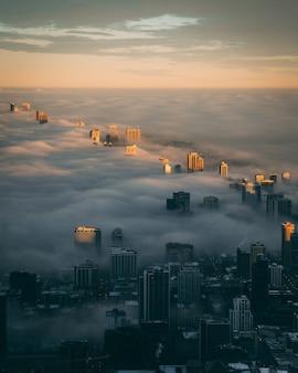 Toits de la ville avec une couche de brouillard au lever du soleil vu d'en haut