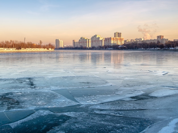 Toits de la ville sur une rivière couverte de glace. la lumière du soleil un soir d'hiver au coucher du soleil. vue depuis les berges de la rivière.
