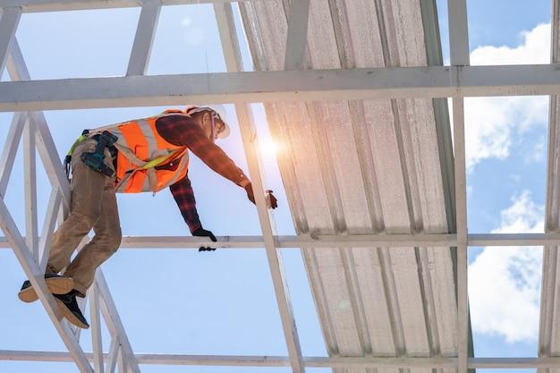 Toiture, ouvriers de la construction portant un harnais de sécurité, vérification et assemblage de l'installation du nouveau toit, outils de toiture.