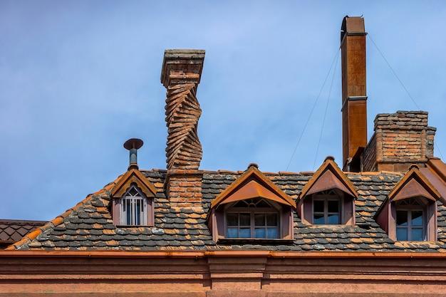 Toiture en tuile d'une vieille maison avec puits de lumière et cheminées