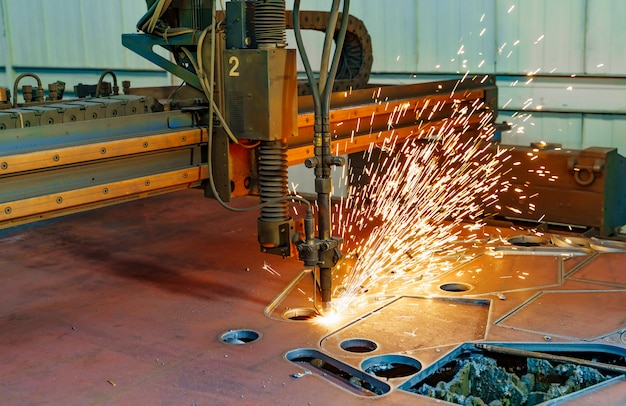 Tôle de découpage laser de haute précision cnc avec étincelle brillante dans une usine industrielle.