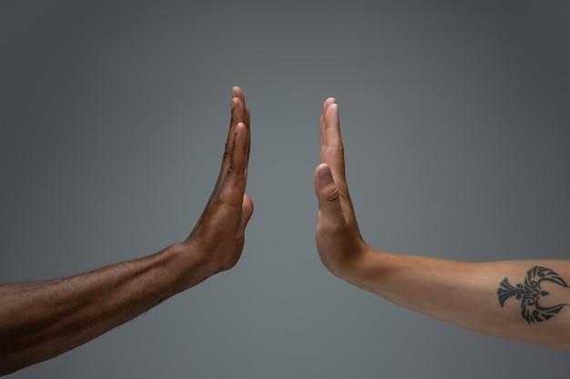 Tolérance raciale. respectez l'unité sociale. mains africaines et caucasiennes gesticulant isolés sur fond gris
