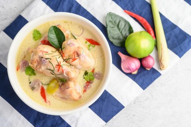 Tom kha kai dans un bol avec des feuilles de lime kaffir, de la citronnelle, de l'oignon rouge, du galanga et du piment.
