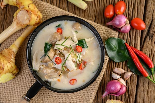 Tom kha kai dans une poêle à frire avec des feuilles de lime kaffir, de la citronnelle, de l'oignon rouge, du galanga et du piment.