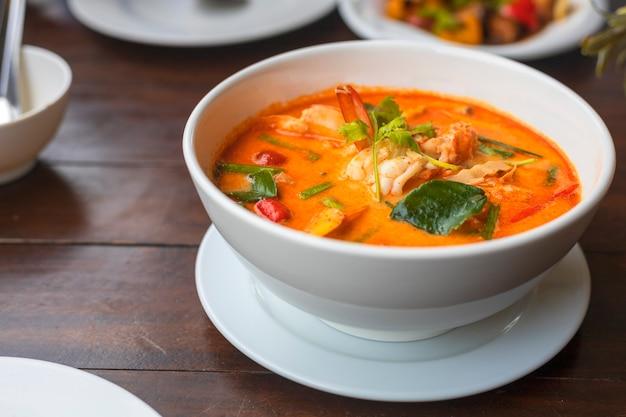 Tom yam kung soupe thaï épicée aux crevettes dans un bol blanc sur table en bois.