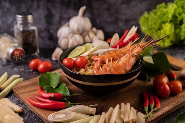 Tom yum kung dans un bol avec tomate, chili, citronnelle, ail, citron et feuilles de lime kaffir