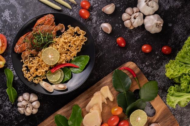 Tom yum mama au crabe avec citron, chili, tomate, ail, citronnelle, feuilles de lime kaffir sur la plaque