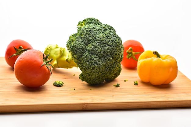 Tomate au poivron jaune et brocoli sur planche à découper en bois