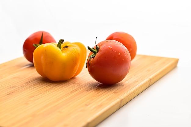 Tomate au poivron jaune sur une planche à découper en bois