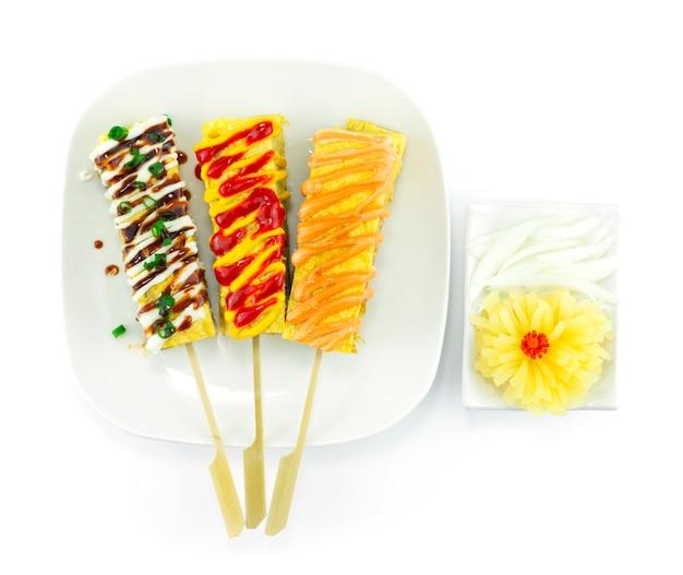 Tomate aux œufs sucrés en brochettes de style japonais sauce au fromage de garniture préférée, crèmes jaunes et sauce kabayaki décorée vue de dessus de radis mariné sculpté