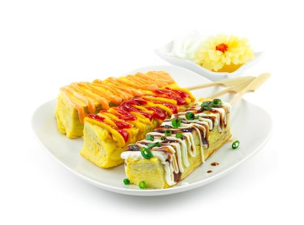 Tomate aux œufs sucrés en brochettes de style japonais sauce au fromage de garniture préférée, crèmes jaunes et sauce kabayaki décorées vue latérale de radis marinés sculptés