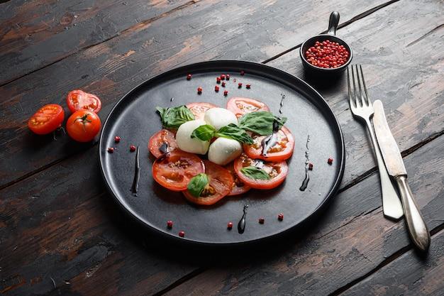 Tomate, basilic, mozzarella salade caprese avec vinaigre balsamique et huile d'olive. vieux fond de planches de bois.