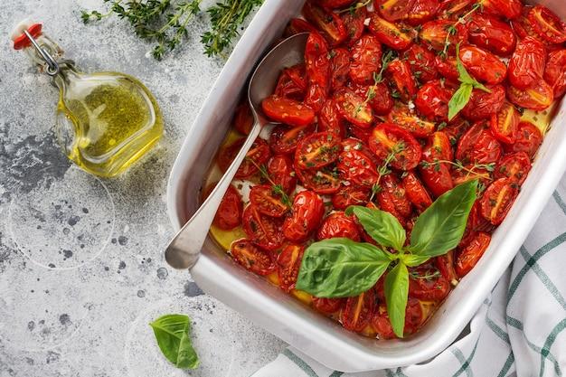 Tomate cerise au four avec l'ail, le thym et le basilic dans une vieille casserole sur fond vintage en béton. vue de dessus.