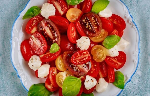 Tomate cerise au fromage mozzarella sur plaque blanche avec fourchette. fermer.