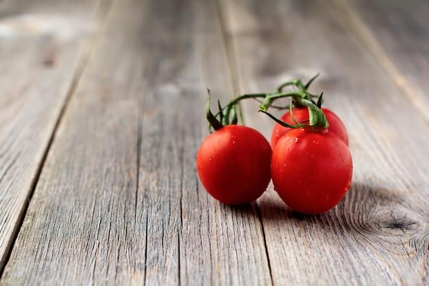 Tomate cerise fraîche sur branche sur fond de bois ancien. mise au point sélective.