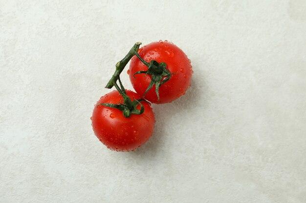 Tomate cerise fraîche sur fond texturé blanc