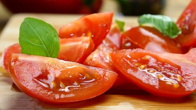 Tomate cerise tranchée en morceaux sur une planche à découper en bois préparation de délicieux plats cuisine à domicile