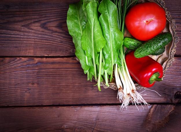 Tomate, concombre et oignon vert sur une plaque de cuivre