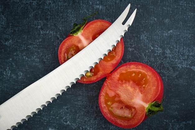 Tomate coupée avec un couteau à tomate spécial, vue de dessus, gros plan
