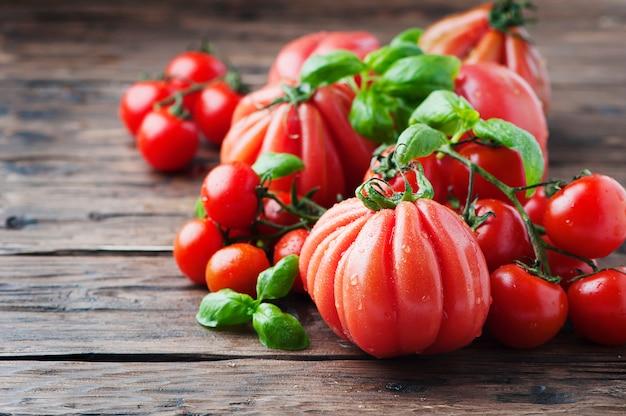 Tomate douce rouge et basilic sur la table en bois