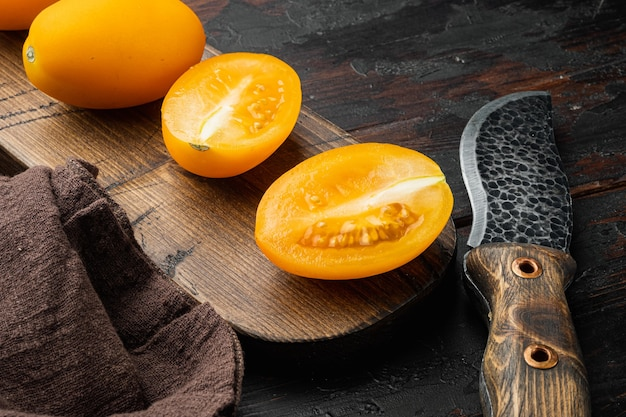 Tomate entière jaune avec un ensemble de tranches, sur le vieux fond de table en bois foncé