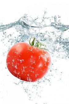 Tomate fraîche tombant dans l'eau