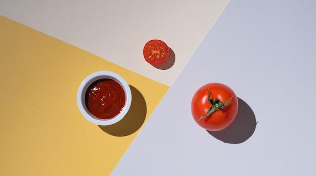 Tomate juteuse fraîche et ketchup sur fond multicolore avec ombre dure