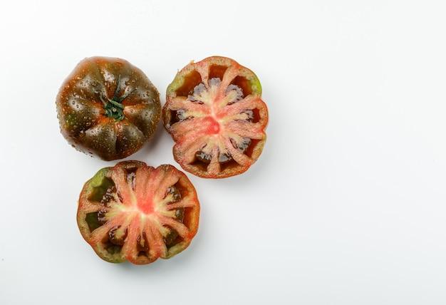 Tomate kumato en tranches sur un mur blanc. mise à plat.