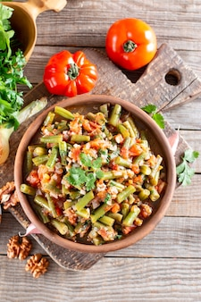 Tomate lobio de gousses de haricots verts dans un bol sur un fond en bois. plat de carême. mise à plat, vue de dessus. fermer