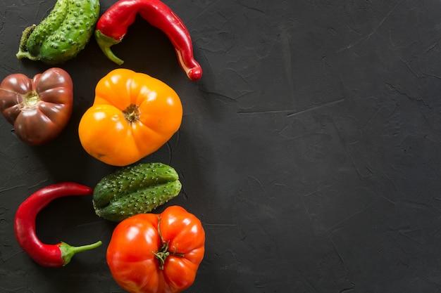 Tomate organique colorée laide, poivron, concombre sur fond noir.