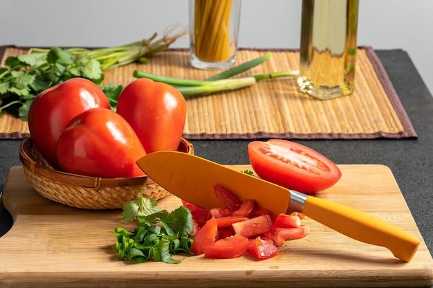Tomate sur une planche de bois avec un couteau ingrédients pour préparer une recette gastronomique