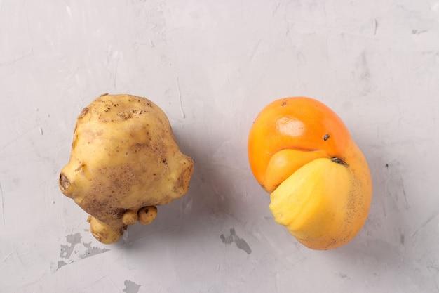 Tomate et pomme de terre laides sur fond gris, gros plan, concept alimentaire laid