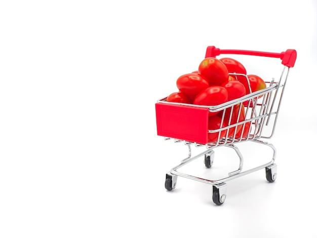 Tomate de raisin ou de cerise fraîche dans un chariot sur fond blanc.