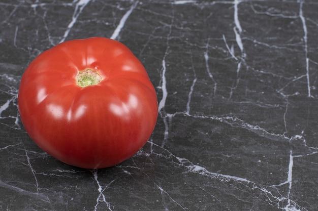 Tomate rouge entière sur marbre.