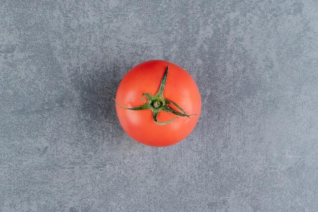 Une tomate rouge fraîche sur une surface en marbre