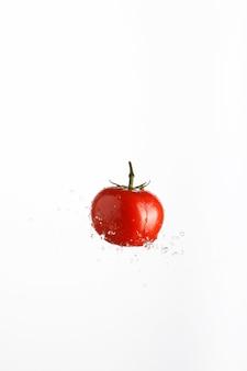Tomate rouge juteuse en jet d'eau