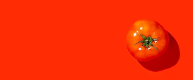 Une tomate rouge mûre sur fond rouge