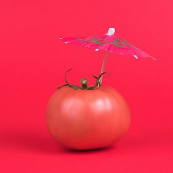 Une tomate rouge avec un parapluie cocktail rouge sur fond rouge.