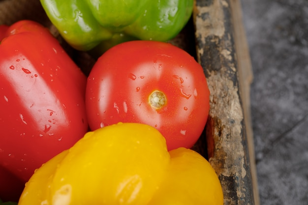 Tomate rouge avec poivrons autour. vue de dessus.