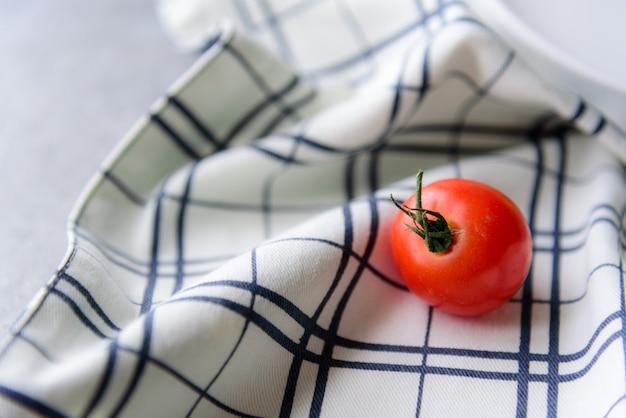 Tomate rouge posée sur une nappe à carreaux noir et blanc.