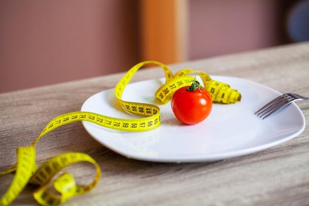 Tomate et ruban à mesurer dans une assiette