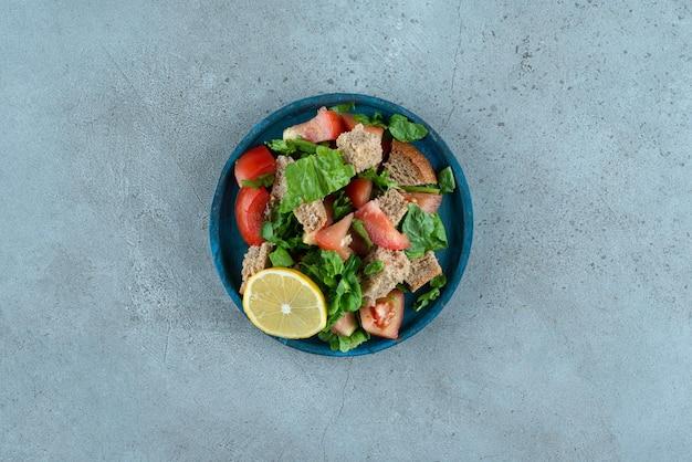 Tomate tranchée, pain, citron et légumes verts sur plaque bleue.