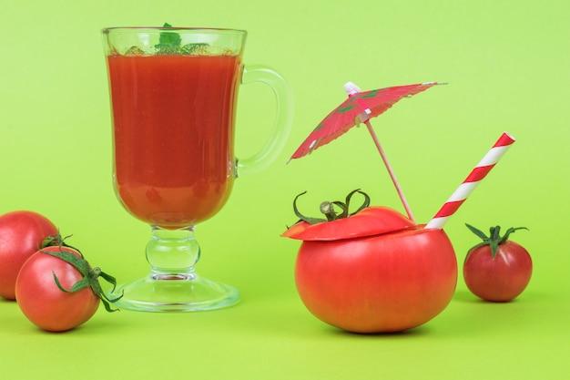 Tomate tranchée avec un tube à cocktail, un verre de jus de tomate et des tomates éparses sur fond vert.