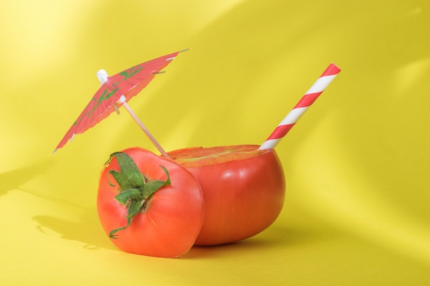 Tomate en tranches avec un parapluie cocktail et une paille à l'ombre des plantes tropicales. le concept de consommation de jus de légumes frais.