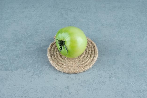 Tomate verte avec corde sur marbre.
