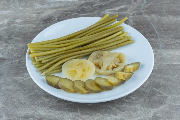 Tomate verte et cueillette de concombre. cornichons tranchés sur plaque blanche.