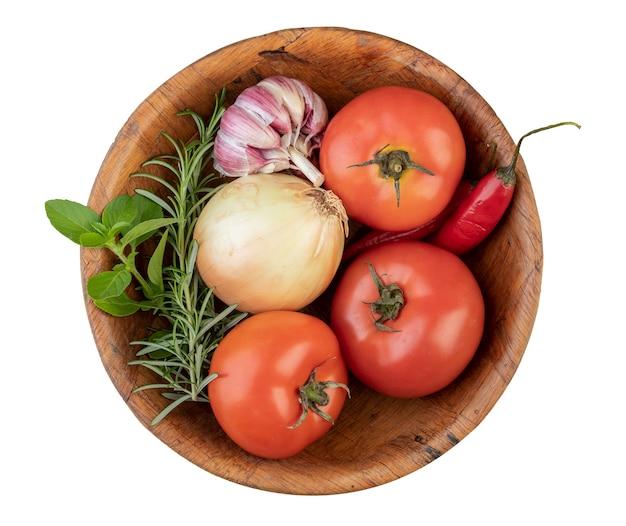 Tomates, ail, poivrons et herbes sur un bol isolé sur.